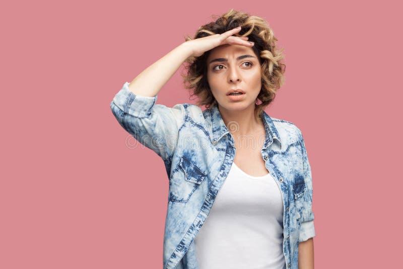 Portret van aandachtige jonge vrouw met krullend kapsel in toevallig blauw overhemd die zich met hand op voorhoofd bevinden en we royalty-vrije stock foto