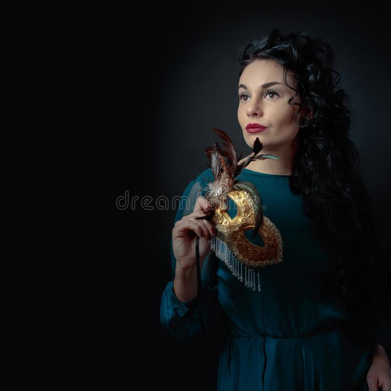 Portret van aantrekkelijk brunette in avondjurk met Carnaval-masker stock afbeelding