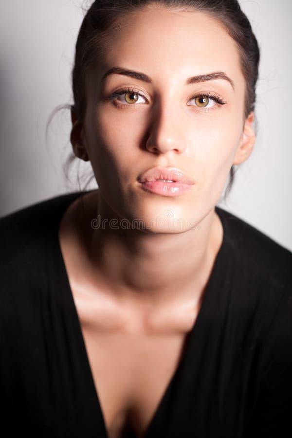 Portret van aantrekkelijk donkerbruin meisje over grijs royalty-vrije stock afbeelding