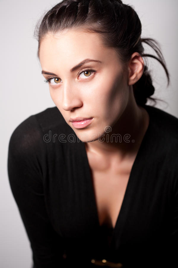 Portret van aantrekkelijk donkerbruin meisje over grijs stock foto