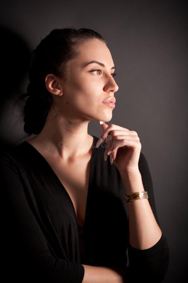 Portret van aantrekkelijk donkerbruin meisje over zwarte royalty-vrije stock foto's
