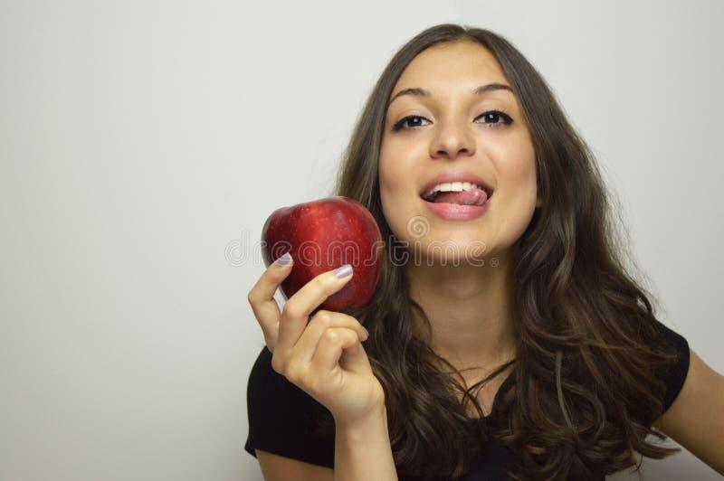 Portret van aantrekkelijk meisje die met rode appel in haar hand gezond fruit glimlachen stock afbeeldingen