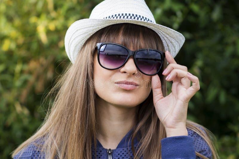 Portret van aantrekkelijk modieus modieus jong meisje in zonnebril en een hoed tegen de achtergrond van groen de zomerpark royalty-vrije stock fotografie