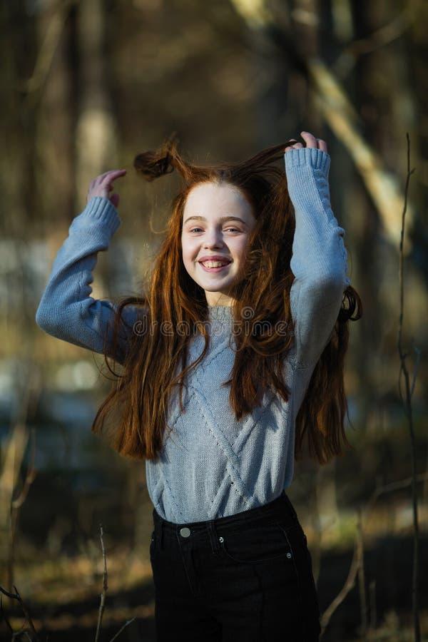 Portret van aantrekkelijk vrolijk tienermeisje met helder rood lang haar stock afbeelding