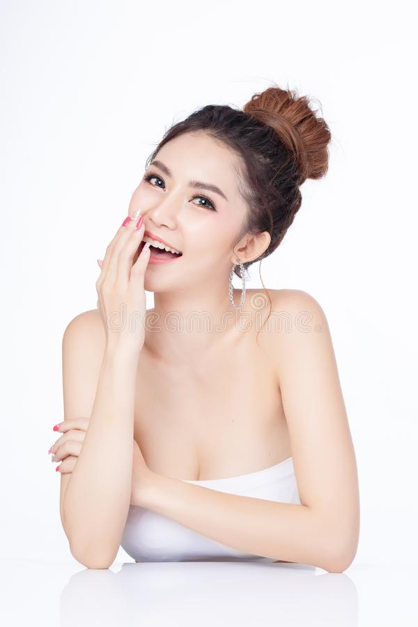 Portret van aantrekkelijke Aziatische vrouwenzitting die op witte achtergrond glimlachen Gezond van de de make-upschoonheid van d stock foto's
