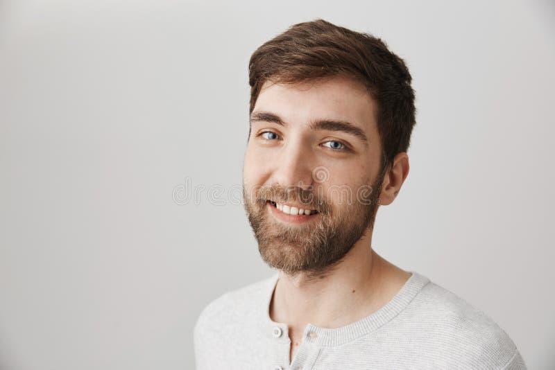 Portret van aantrekkelijke charmante gebaarde kerel met vriendelijke glimlach status helft-gedraaid over grijze achtergrond, het  stock afbeeldingen