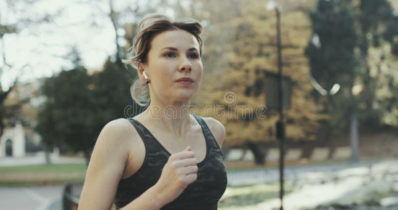 Portret van aantrekkelijke donkerbruine vrouwelijke agent die in de hoofdtelefoonsoortelefoons van het stadspark airpods bluetoot royalty-vrije stock foto's