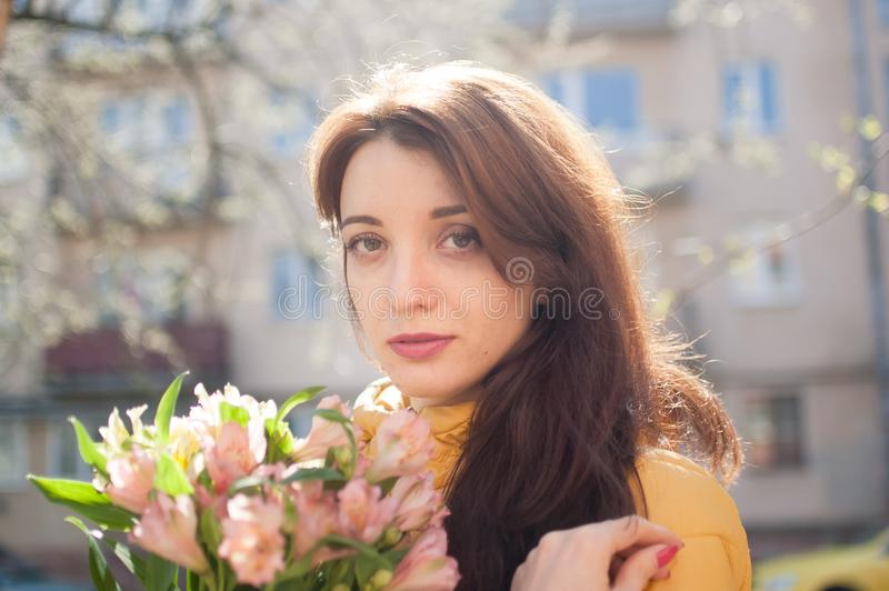 Portret van aantrekkelijke en mooie jonge vrouw die in geel jasje een groot boeket van kleurrijke bloemen in openlucht houden stock foto