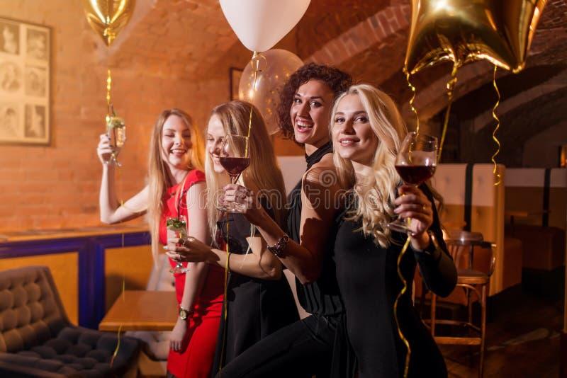 Portret van aantrekkelijke goed-geklede jonge vrouwen die met glazen alcoholische dranken hebbend pret bij de partij binnen lache royalty-vrije stock foto's