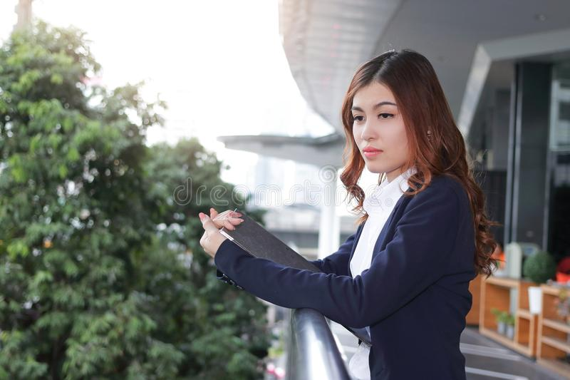 Portret van aantrekkelijke jonge Aziatische bedrijfsvrouw met documentomslag die en iets bevinden denken zich bij balkon van bure stock fotografie