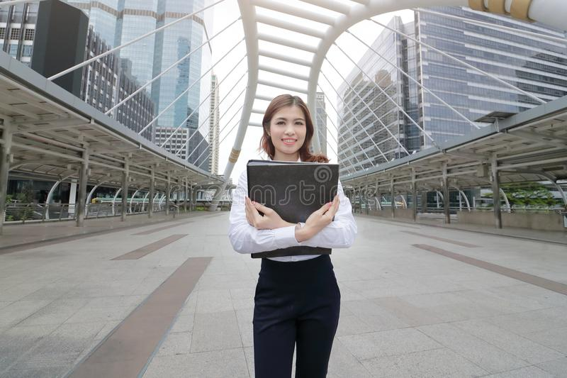 Portret van aantrekkelijke jonge Aziatische het documentomslag van de bedrijfsvrouwenholding bij stoep van stedelijke stadsachter royalty-vrije stock fotografie