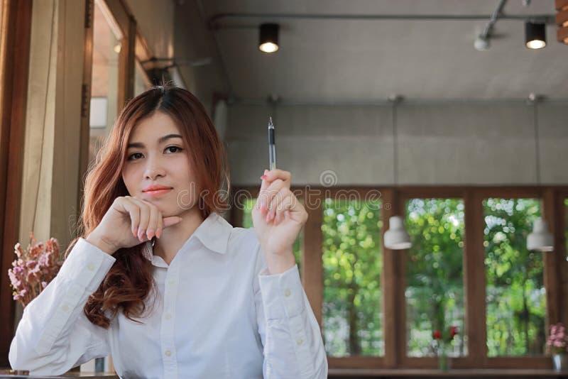 Portret van aantrekkelijke jonge Aziatische onderneemster die een pen in haar handen houden en camera in koffiewinkel bekijken me royalty-vrije stock foto