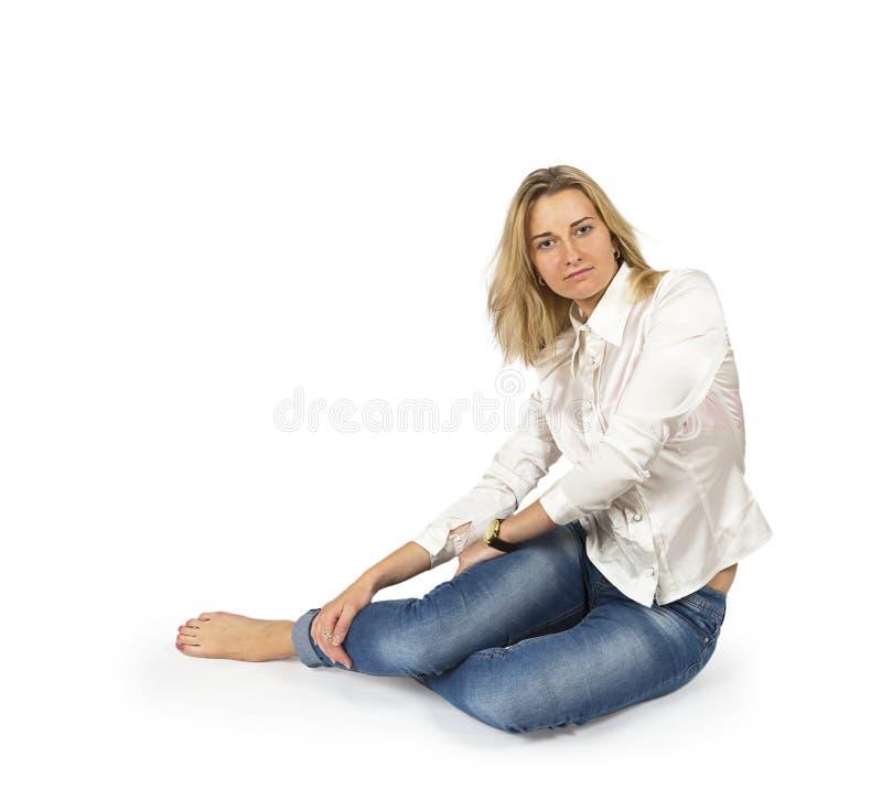 Portret van aantrekkelijke jonge blonde vrouwenzitting op vloer stock fotografie