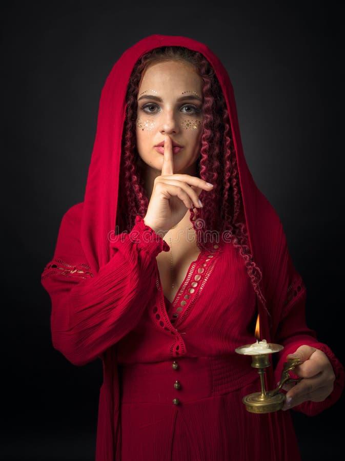 Portret van aantrekkelijke jonge vrouw in een buitensporige rode kleding met koperkandelaar en brandende kaars royalty-vrije stock foto
