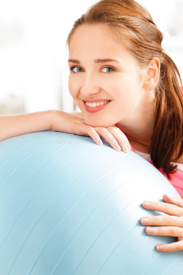 Portret van aantrekkelijke jonge vrouw het ontspannen geschiktheidsbal bij gymnastiek stock fotografie