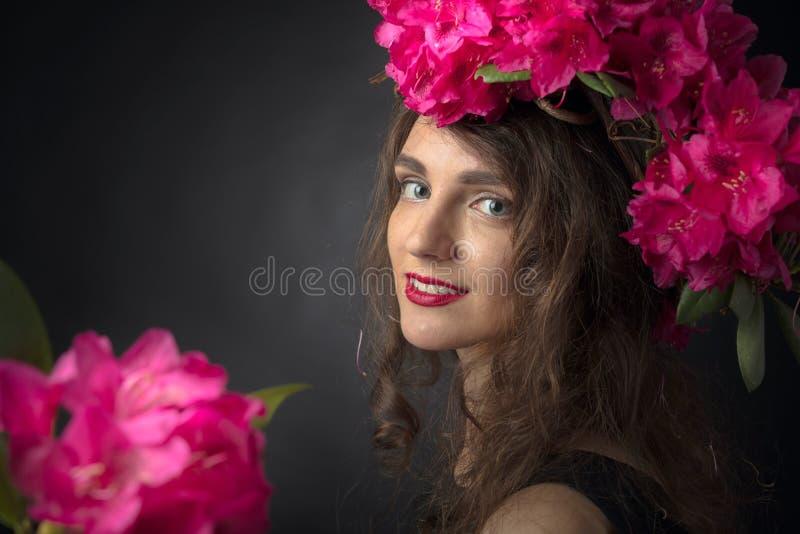 Portret van aantrekkelijke jonge vrouw met lang krullend haar en kroon op een hoofd stock afbeelding