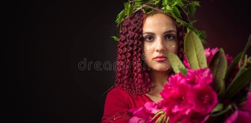 Portret van aantrekkelijke jonge vrouw in rode kleding met boeket van rode rododendron en kroon op een hoofd royalty-vrije stock afbeeldingen