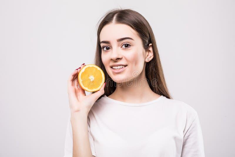 Portret van aantrekkelijke Kaukasische glimlachende die vrouw met sinaasappel op witte achtergrond wordt geïsoleerd Het concept v royalty-vrije stock afbeeldingen