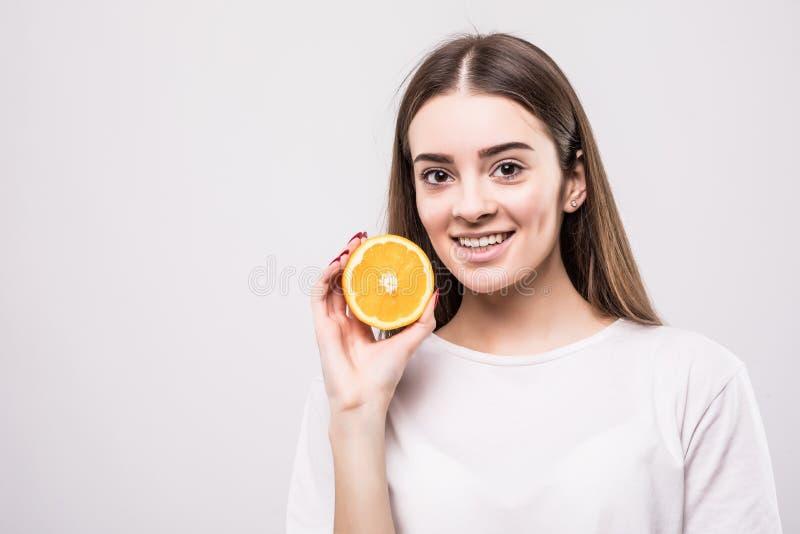 Portret van aantrekkelijke Kaukasische glimlachende die vrouw met sinaasappel op witte achtergrond wordt geïsoleerd Het concept v royalty-vrije stock fotografie