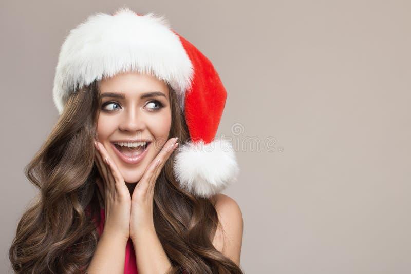 Portret van aantrekkelijke leuke verraste vrouw in santahoed stock afbeeldingen