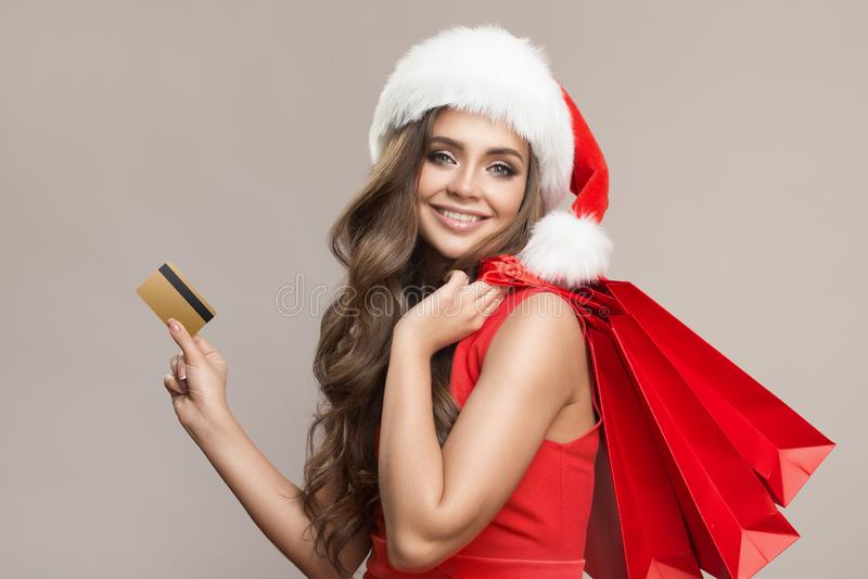Portret van aantrekkelijke leuke vrouw in de holding van de santahoed het winkelen zakken en creditcard royalty-vrije stock afbeelding