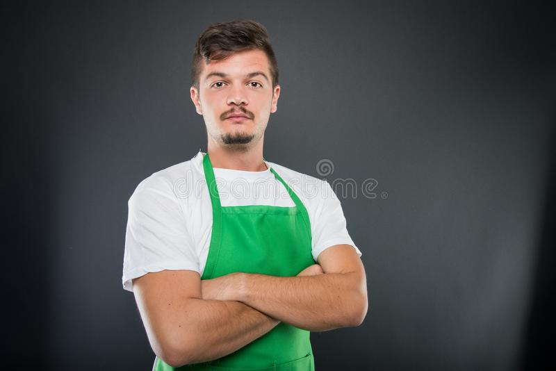 Portret van aantrekkelijke mannelijke supermarktwerkgever met wapenskruis royalty-vrije stock afbeeldingen