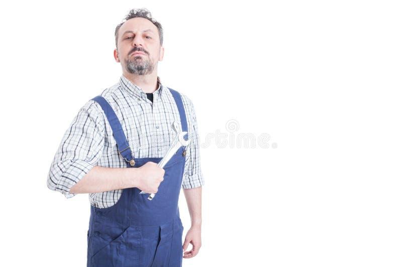 Portret van aantrekkelijke mannelijke werktuigkundige die in blauwe overall wr houden royalty-vrije stock foto