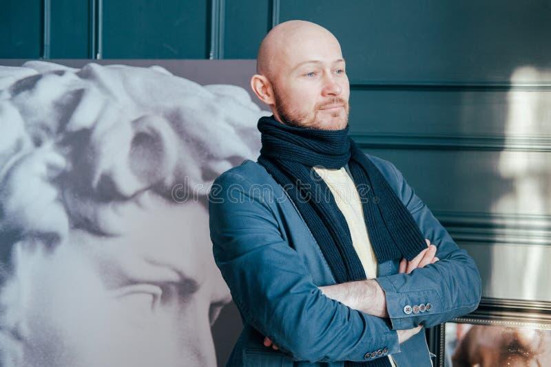 Portret van aantrekkelijke volwassen succesvolle kale de criticushistoricus van de mensenkunst met baard in sjaal in kunstgalerie royalty-vrije stock afbeelding