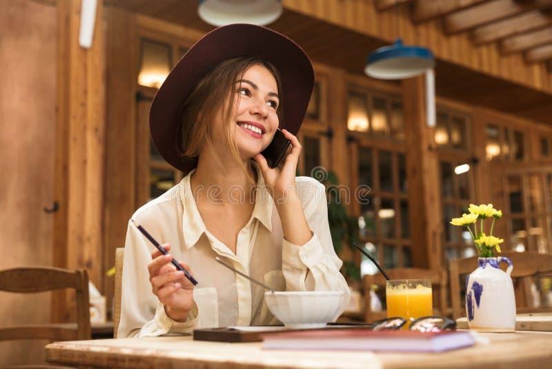 Portret van aantrekkelijke vrouw die hoed dragen die op smartphone spreken royalty-vrije stock afbeeldingen