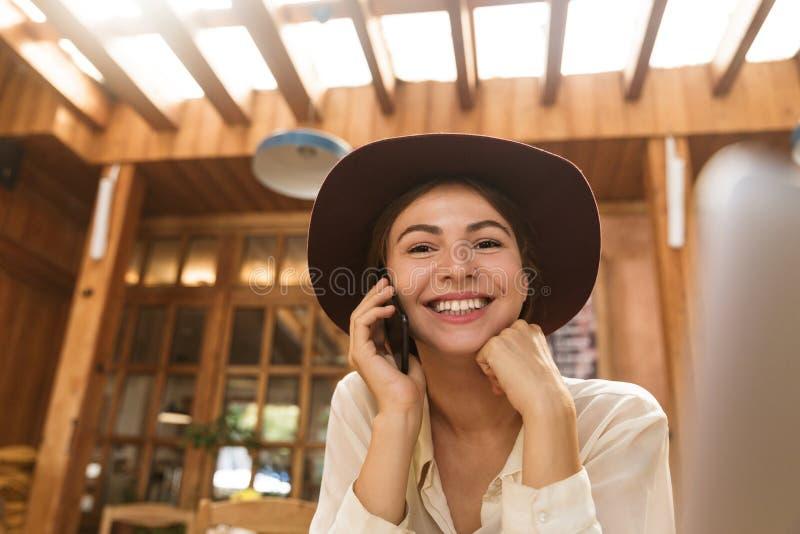 Portret van aantrekkelijke vrouw die hoed dragen die op smartphone spreken stock foto
