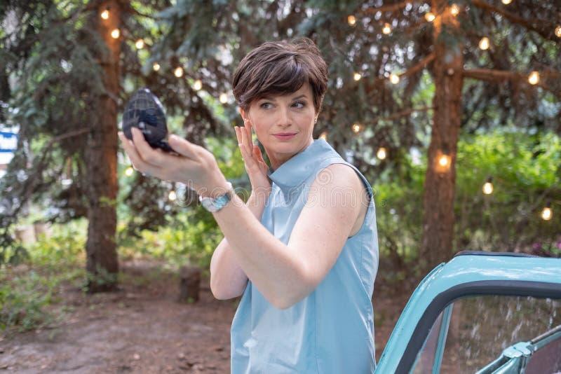 Portret van aantrekkelijke vrouw Leuke bedrijfsvrouw die of haar samenstelling op openlucht aanpassen verbeteren royalty-vrije stock fotografie