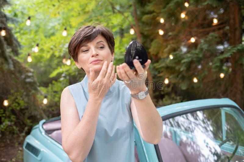 Portret van aantrekkelijke vrouw Leuke bedrijfsvrouw die of haar samenstelling op openlucht aanpassen verbeteren royalty-vrije stock afbeeldingen