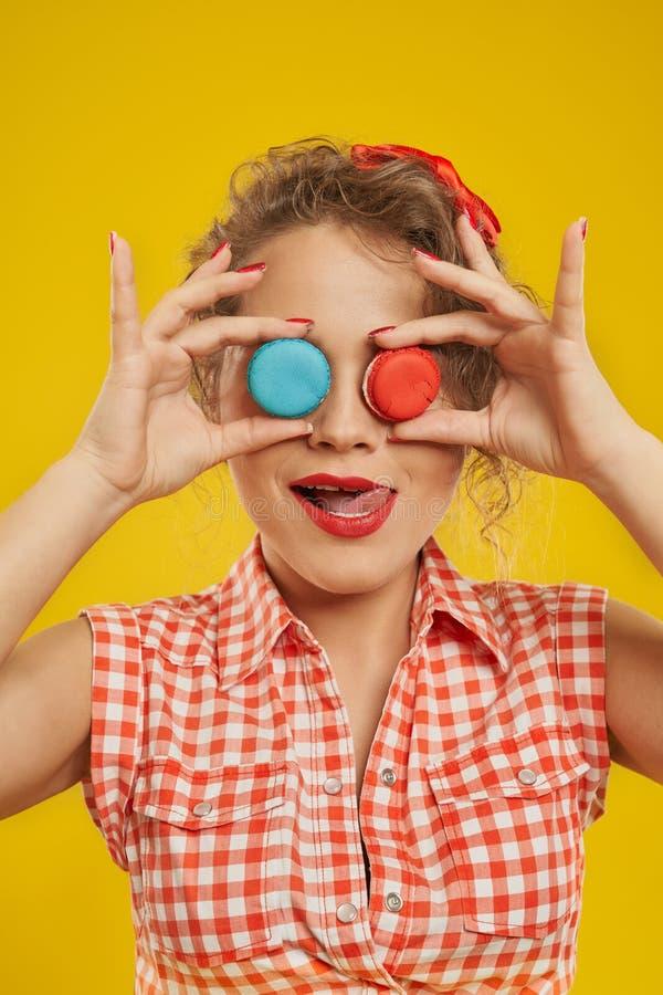 Portret van aardig meisje dat haar ogen bedekt met macaroons royalty-vrije stock foto's