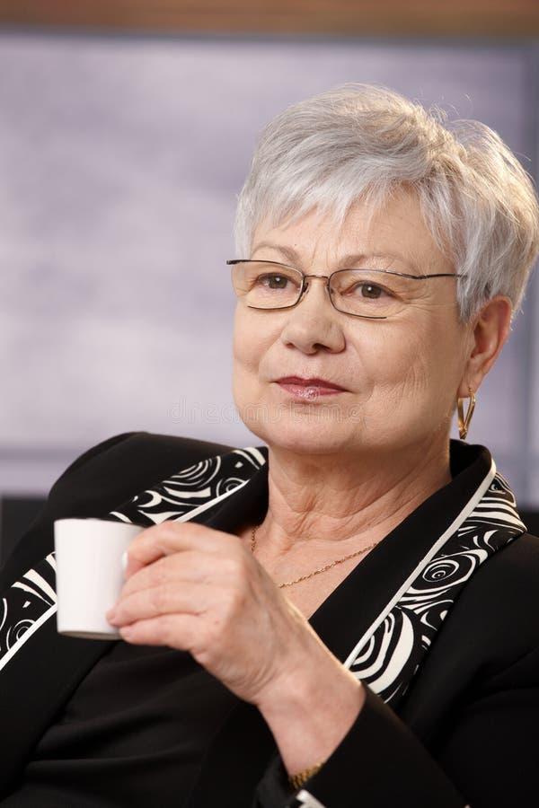 Portret van aardige hogere vrouw die koffie heeft royalty-vrije stock fotografie