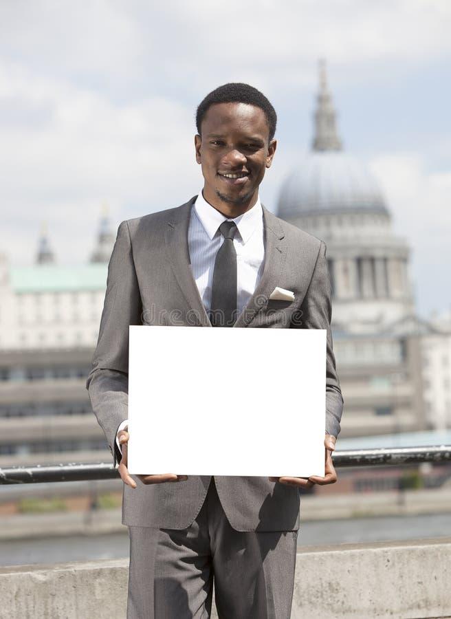Portret van Afrikaanse Amerikaanse zakenman die en leeg karton glimlachen houden royalty-vrije stock foto's