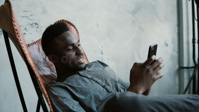 Portret van Afrikaanse mensenzitting als voorzitter, die Smartphone gebruiken Het knappe mannetje glimlacht en bekijkt foto's in  royalty-vrije stock fotografie