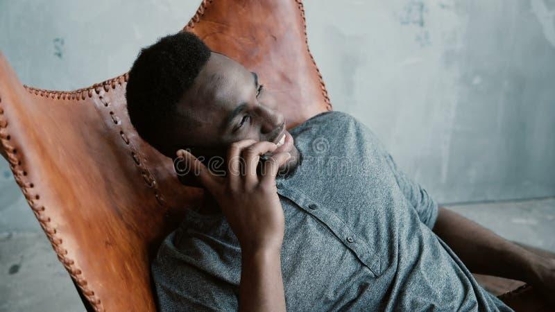 Portret van Afrikaanse mensenzitting als voorzitter en sprekend op Smartphone Het mannetje lacht bij grap, die grote tijd hebben stock afbeelding