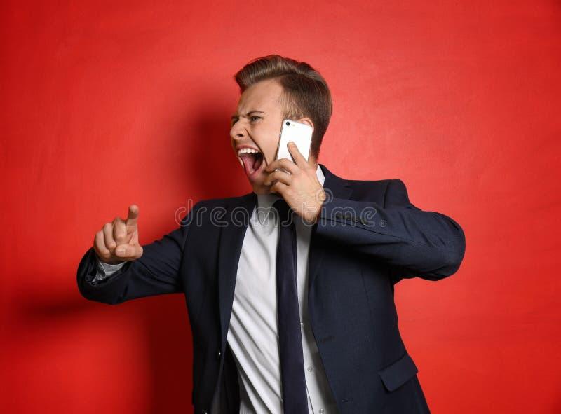 Portret van agressieve jonge zakenman met mobiele telefoon op kleurenachtergrond royalty-vrije stock foto