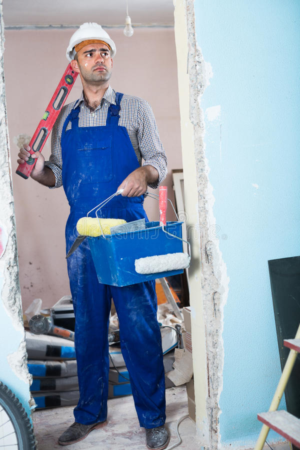 Portret van arbeider dat zich met waterpas en bucke bevindt royalty-vrije stock afbeeldingen