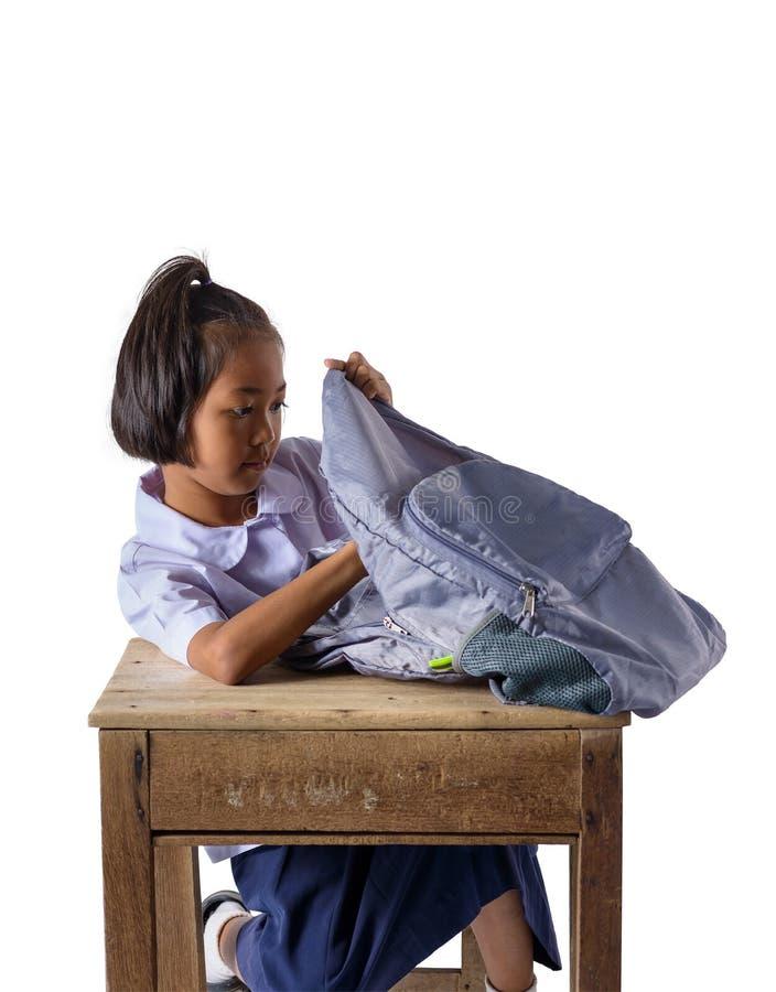Portret van Aziatisch meisje in school het eenvormige Kijken in de rugzak die op witte achtergrond wordt geïsoleerd stock afbeelding