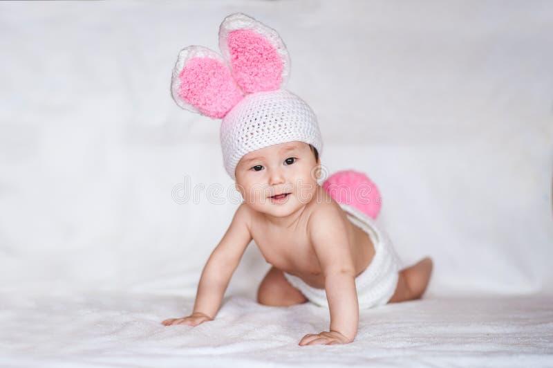 Portret van Aziatische baby in hoed met konijnoren op witte achtergrond stock afbeeldingen