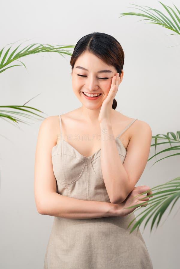 Portret van Aziatische gelukkige vrouw status met groene bladeren rond haar op witte achtergrond stock afbeeldingen