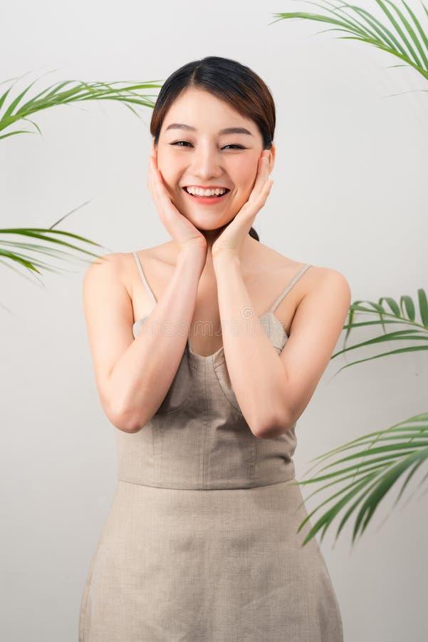 Portret van Aziatische gelukkige vrouw status met groene bladeren rond haar op witte achtergrond royalty-vrije stock afbeeldingen