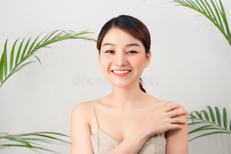Portret van Aziatische gelukkige vrouw status met groene bladeren rond haar op witte achtergrond royalty-vrije stock fotografie