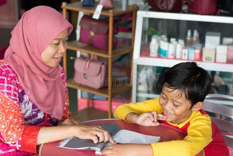 Portret van Aziatische hijab moslimmoeder die wat verklaren binnenkanttijdschrift aan zoon royalty-vrije stock fotografie