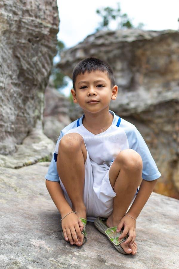 Portret van Aziatische jongenszitting op een rots royalty-vrije stock afbeeldingen