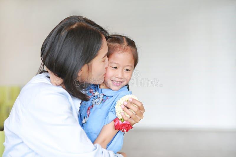 Portret van Aziatische moeder die haar dochter zoent en knuffelt op moederdag in Thailand Klein meisje Betaal respect royalty-vrije stock afbeeldingen