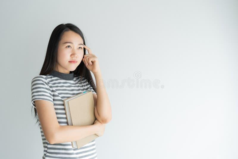 Portret van Aziatische vrouw die en notitieboekje op witte achtergrond denken houden royalty-vrije stock afbeeldingen