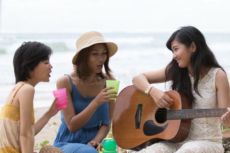 Portret van Aziatische vrouw en van de vriendengroep het spelen gitaar en hap stock foto
