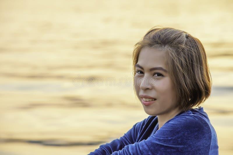 Portret van Aziatische vrouwenzitting door de rivier en het weerspiegelde lichte goud in water stock foto's